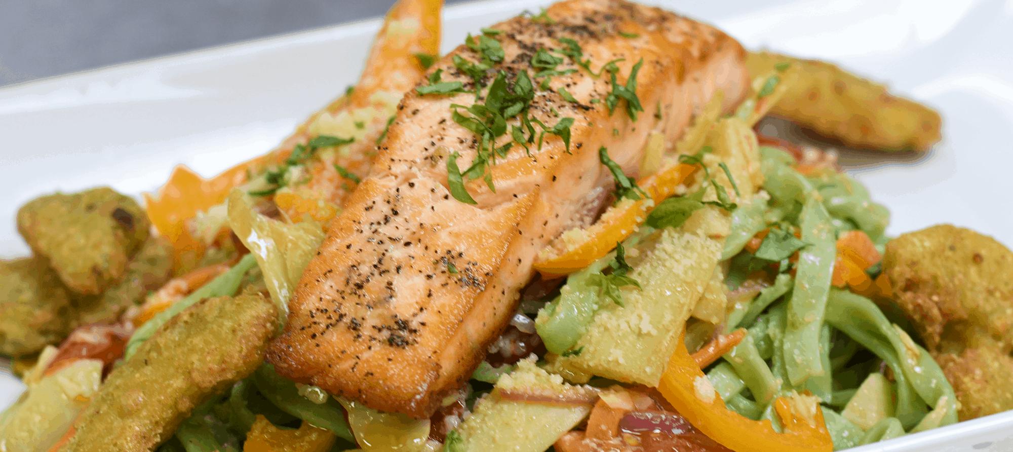 Grilled Capri Salmon, Served with Vegetable Fettuccini Noodles, Sautéed Mediterranean Vegetables, Fresh Herbs, Extra Virgin Olive Oil, & Garlic
